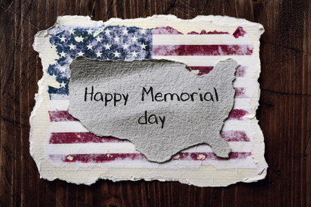 an american flag and the text happy memorial day in a piece of paper in the shape of the map of the United States, on a wooden background