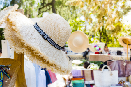 closeup of some different fashion accessories and clothes on sale in a street market, highlighting some straw hats in the foreground