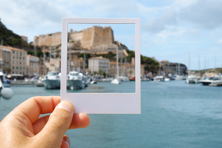 closeup of a young caucasian man at the port of Bonifacio, in Corsica, France, with a white frame in his hand framing its famous citadel, simulating an instant photograph Stock Photo