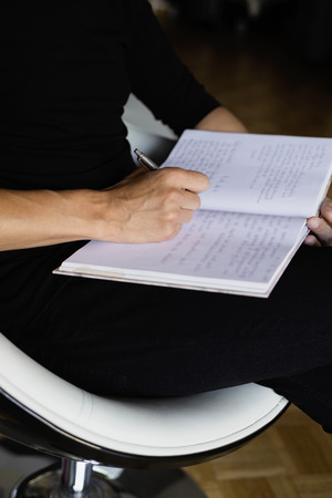 closeup of a young caucasian man, wearing black casual clothes, writing with a pen in a notebook sitting in a chair indoors