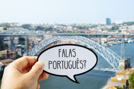the hand of a man holding a speech bubble with the question falas portugues, do you speak Portuguese? written in Portuguese, in Porto, Portugal, with the famous Dom Luis I Bridge in the background