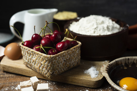 closeup of the ingredients to prepare a coca de cireres, a cherry sweet flat cake typical of Catalonia, Spain, such as wheat flour, milk, sugar, eggs or butter, on a wooden table