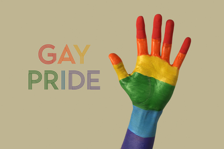 closeup of the palm of the hand of a person, painted as the rainbow flag, and the text gay pride written with the colors of the rainbow flag, against an off-white background Stock Photo