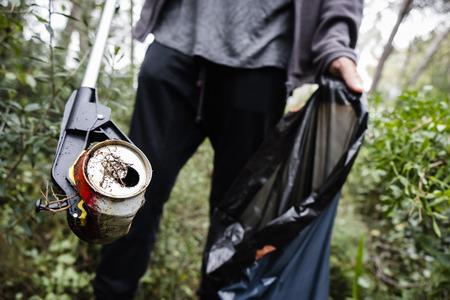 primo piano di un uomo caucasico che raccoglie spazzatura con un bastoncino di raccolta della spazzatura, in una foresta, come azione per pulire l'ambiente naturale