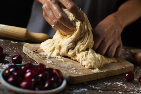 closeup of a young caucasian man kneading a piece of dough to prepare a coca de cireres, a cherry sweet flat cake typical of Catalonia, Spain, on a wooden table