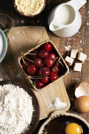 high angle view of the ingredients to prepare a coca de cireres, a cherry sweet flat cake typical of Catalonia, Spain, such as wheat flour, milk, sugar, eggs or butter, on a wooden table Imagens