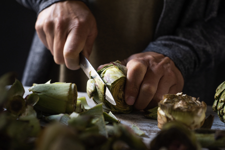 closeup of a caucasian man cutting with a kitchen knife some raw fresh artichokes, on a white rustic wooden table