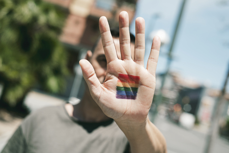 closeup of a young caucasian person with a rainbow flag in the palm of his or her hand, in front of his or her face, on the street at daytime Stock Photo