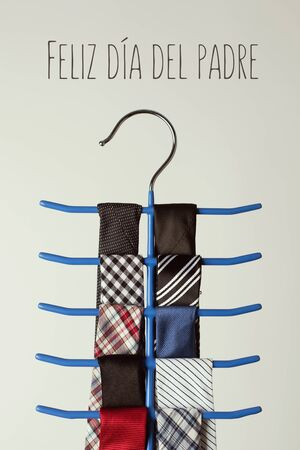 the text feliz dia del padre, happy fathers day written in spanish, and a necktie hanger with some neckties of different colors and patterns, on an off-white background