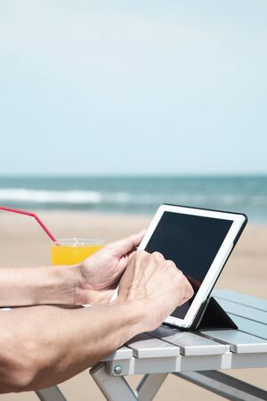 closeup of a young caucasian man on the beach, using a digital tablet, sitting at an outdoors table, next to a glass with a refreshing orange drink, and some blank space on top