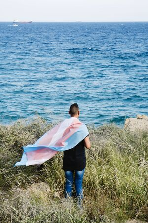 a young caucasian person, seen from behind, draping a transgender pride flag over his or her shoulders, facing the ocean Stock Photo