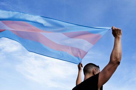 Un joven caucásico, visto desde atrás, sosteniendo una bandera del orgullo sobre su cabeza contra el cielo azul