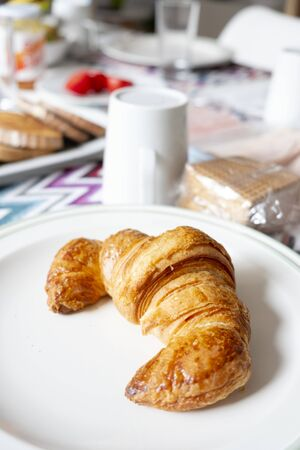 closeup of a croissant in a plate on a table set for breakfast, next to a white ceramic pot with milk and some trays with toasts and cold cuts