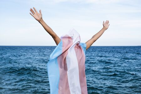 a young caucasian person covered with a transgender pride flag with his or her arms open in the air, with the ocean in the background