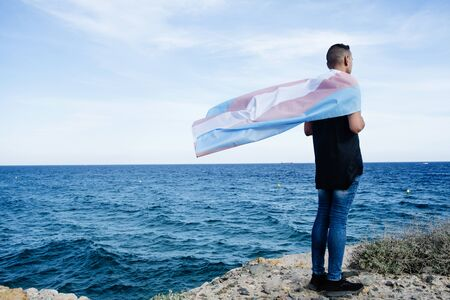 A young Caucasian person, seen from behind, draping a transgender pride flag over his or her shoulders, facing the ocean Imagens
