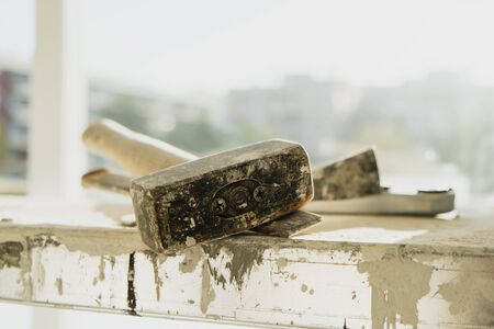 closeup of a rusty metal mallet and a cold chisel, on a working platform stained with paint and plaster, in a building