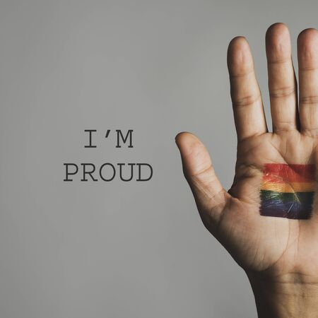 closeup of the palm of the hand of a person, with a rainbow flag in it, and the text I am proud against an off-white background