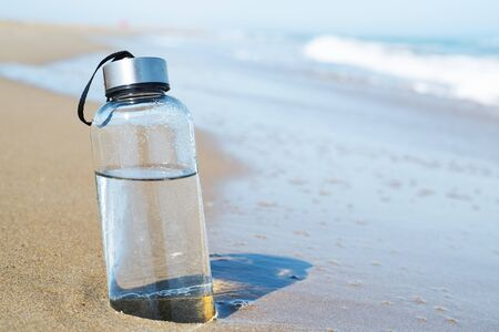 closeup of a glass reusable water bottle on the seashore of a lonely beach 版權商用圖片 - 126018623