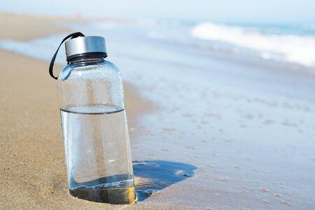 Nahaufnahme einer wiederverwendbaren Wasserflasche aus Glas an der Küste eines einsamen Strandes