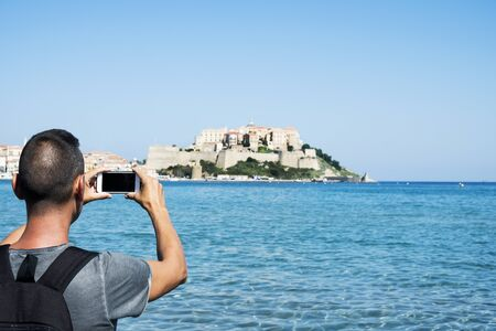 a young caucasian man, seen from behind, taking a picture of Calvi, in Corsica, France, with the Mediterranean sea in the foreground and the citadel of Calvi in the background