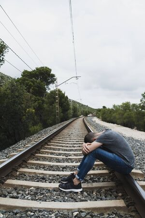 a caucasian man, wearing casual clothes, curled up on the railroad tracks, in a natural landscape