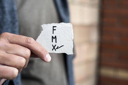 Primer plano de un joven caucásico sosteniendo un trozo de papel con las letras F para mujer, M para hombre y X para la tercera categoría de género, escrito en él, con una marca de verificación en la X Foto de archivo