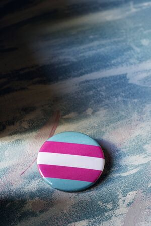 closeup of a badge patterned with a transgender pride flag on a surface painted with brushstrokes of different colors