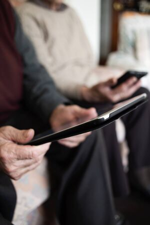 closeup of an old caucasian man using a tablet and an old caucasian man using a smartphone, sitting both in a couch Stok Fotoğraf