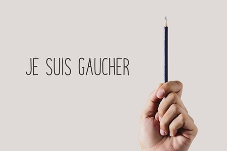closeup of a young left-handed man with a pencil and the text je suis gaucher, I am left-handed written in French, on an off-white background Stok Fotoğraf