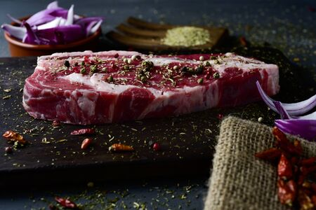 closeup of a raw strip steak seasoned with different spices, such pepper corns of different colors or oregano, on a dark wooden tray, on a table, next to a bowl with chopped purple onion Stok Fotoğraf