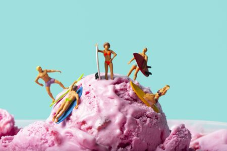 closeup of some miniature people in swimsuit surfing on a strawberry ice cream ball, against a blue background with some blank space Stockfoto