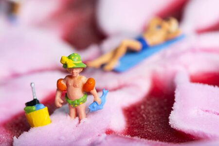closeup of a miniature child playing on a strawberry ice cream, and a miniature man in swimsuit relaxing on a beach towel in the background