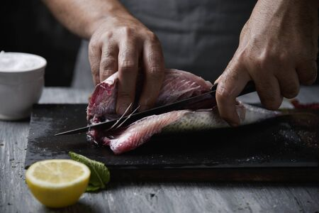 closeup of a young caucasian man cutting a raw fresh mackerel with a knife, on a slate tray placed on a rustic wooden table or countertop