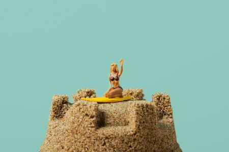 closeup of a miniature woman in swimsuit, kneeling on a surfboard, on the top of a sandcastle, against a blue background with a large blank space on top Stok Fotoğraf