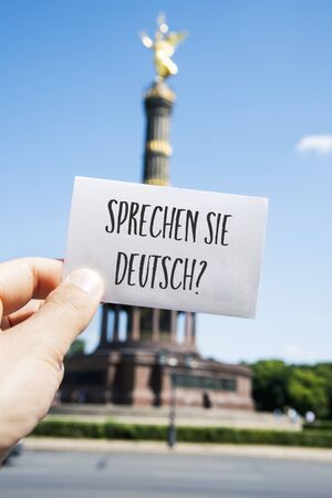 closeup of the hand of a young caucasian man showing a speech bubble with the question sprechen sie deutsch, do you speak german written in german, in front of the Victory Column in Berlin, Germany Stok Fotoğraf