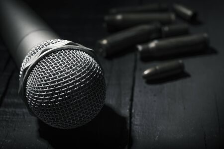 closeup of a microphone on a dark gray rustic surface and some bullets and bullet shells in the background Stok Fotoğraf