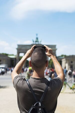 closeup of a young caucasian man, seen from behind, taking a picture of the popular Brandenburg Gate in Berlin, Germany, with his smartphone