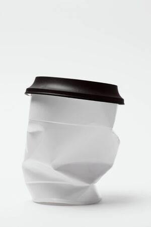 closeup of a smashed white plastic cup, covered with a black lid, on a white background with some blank space on top