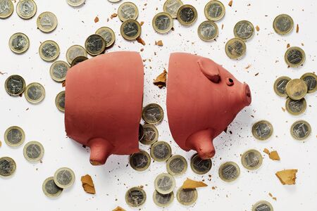 high angle view of a broken piggy bank and many euro coins on a white surface