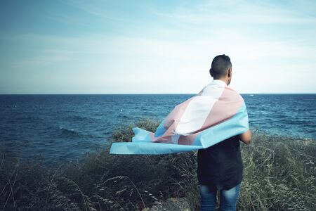 a young caucasian person, seen from behind, draping a transgender pride flag over his or her shoulders, facing the ocean Stok Fotoğraf