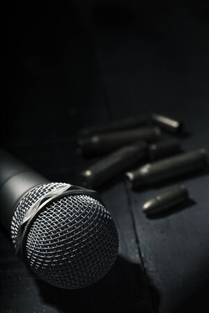 closeup of a microphone on a dark gray rustic surface and some bullets and bullet shells in the background, with some blank space on top