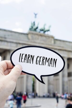 closeup of the hand of a young man showing a speech bubble with the text learn German written in it, in front of the Brandenburg Gate in Berlin, Germany