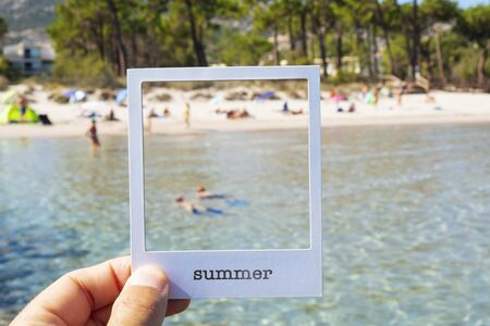 closeup of a man holding a white paperboard frame, with the word summer written in it, framing a beach with unrecognizable people, simulating to be an instant photo