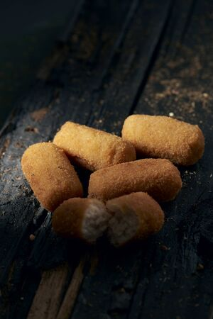 closeup of some spanish croquettes on a dark rustic wooden table