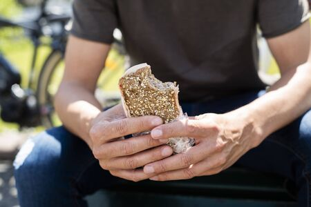 closeup of a young caucasian man, wearing denim jeans and a t-shirt, eating a turkey sandwich while sitting on a park, next to some bicycles in the background Stok Fotoğraf
