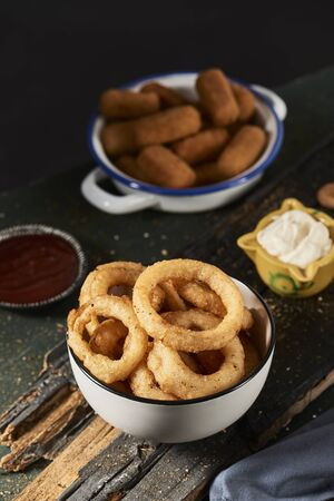 some calamares a la romana, fried battered squid rings typical of spain, in a white bowl and some spanish croquettes in a white and blue enamel plate on a table, next to a mortar with aioli sauce Stok Fotoğraf