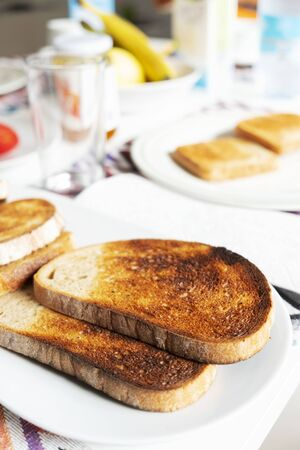 closeup of some toasts in a white ceramic plate on a table set for breakfast or dinner