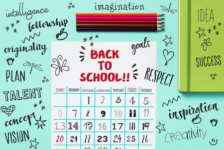 high angle view of a calendar with the text back to school on a blue table, next to some pencil crayons of different colors and a green notepad, and some drawings and school related words