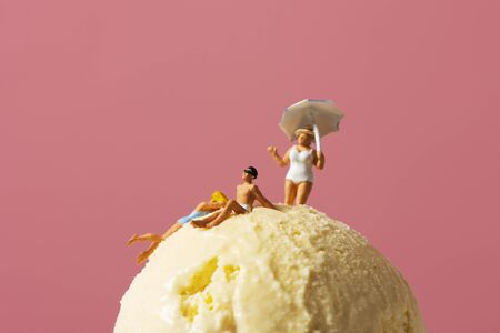 some miniature people wearing swimsuit relaxing on an ice cream ball, against a pink background with some blank space around them