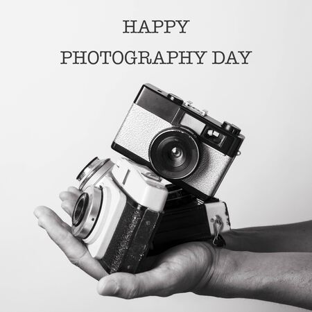 closeup of the hand of a caucasian man holding some retro film cameras and the text happy photography day, in black and white